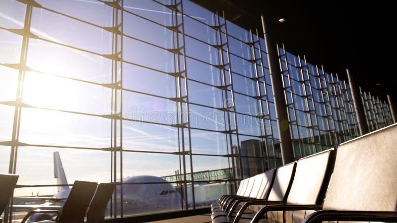 Sillas vacías en el terminal de aeropuerto iluminado por el sol, avión que se coloca detrás de la ventana, subiendo fotos de archivo