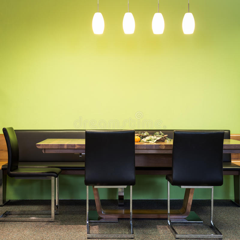 Sillas voladizas en la tabla de la madera con las lámparas imagen de archivo