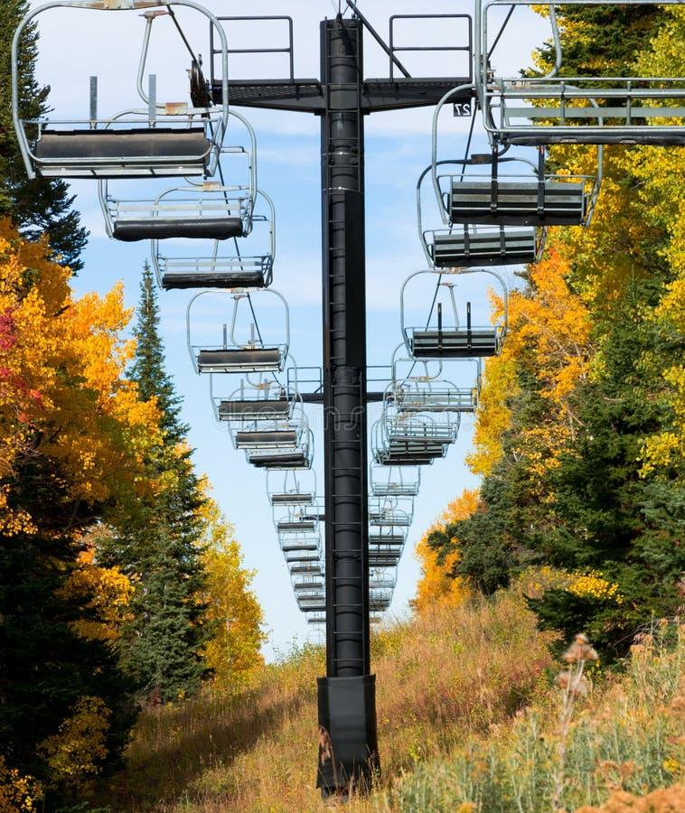 Sillas y follaje de otoño vacíos del remonte foto de archivo