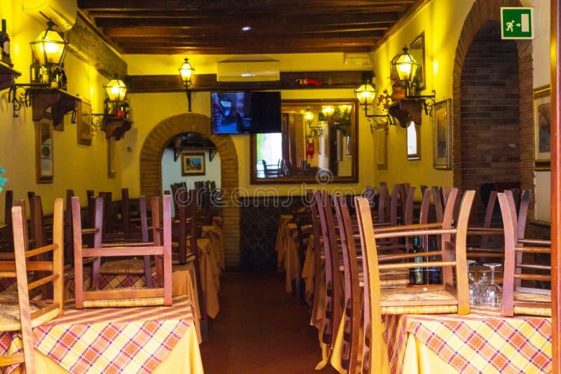 Sillas y mesas apiladas en un restaurante cerrado Roma fotografía de archivo