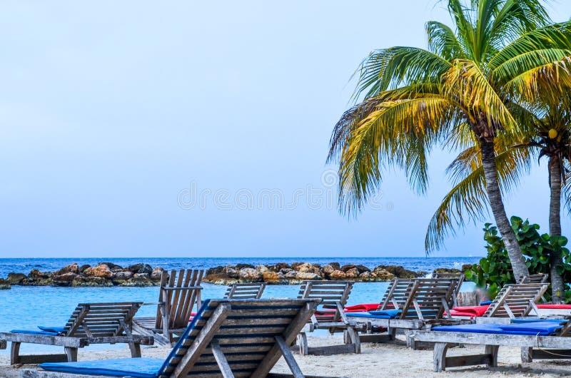 Sillas y palmera de playa por el mar fotos de archivo