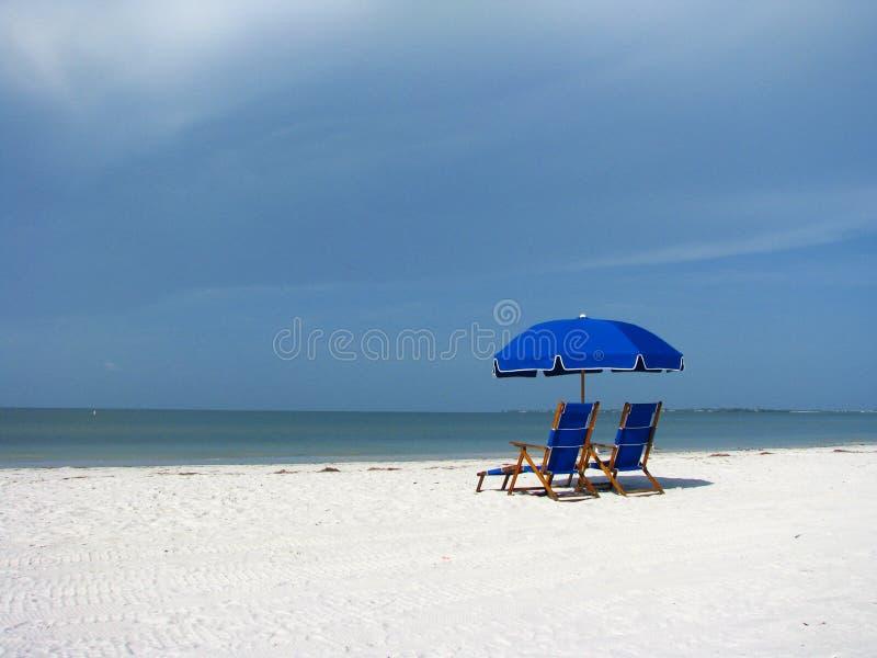 Sillas y paraguas de playa en la playa imagenes de archivo