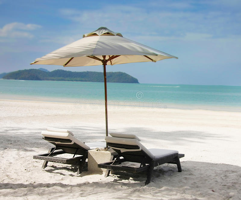 Sillas y paraguas en la playa fotografía de archivo