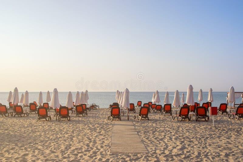 Sillas y paraguas en una playa hermosa en la salida del sol en Sunny Beach en la costa del Mar Negro de Bulgaria imagenes de archivo