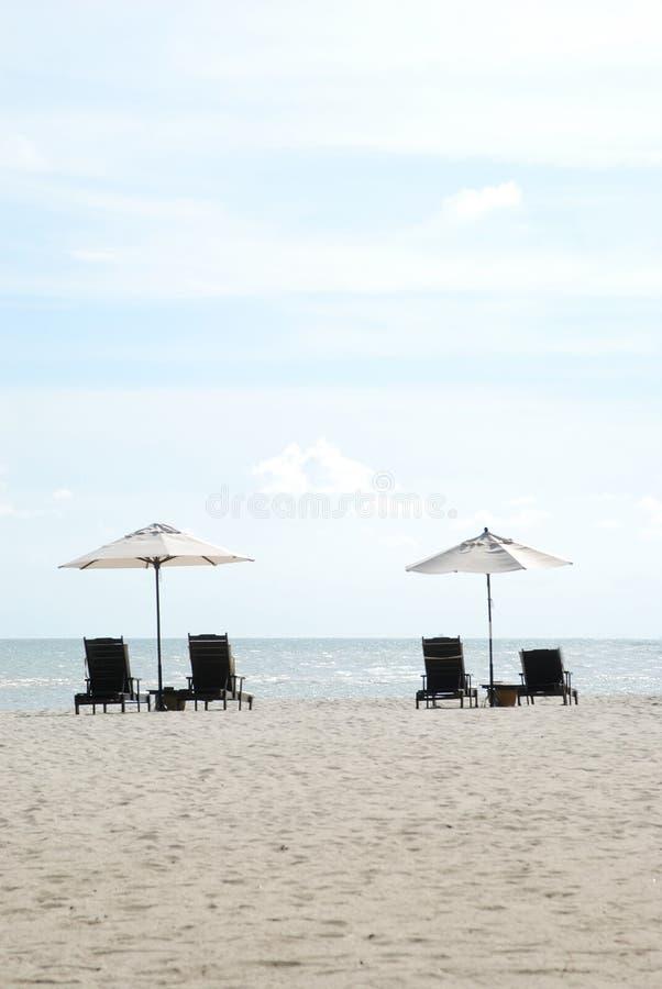 Sillas y paraguas por la playa fotos de archivo libres de regalías