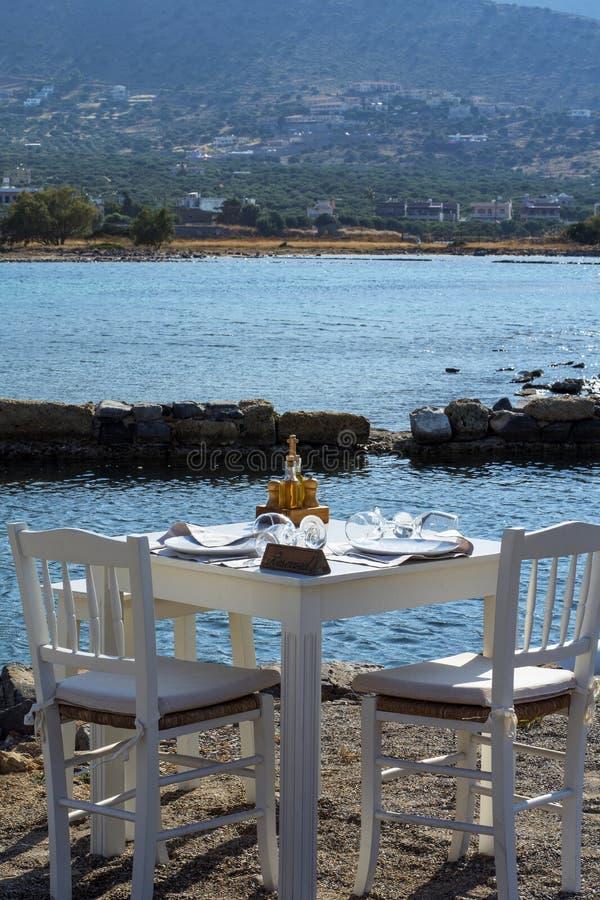 Sillas y tabla blancas del restaurante de la calle cerca del mar imagen de archivo
