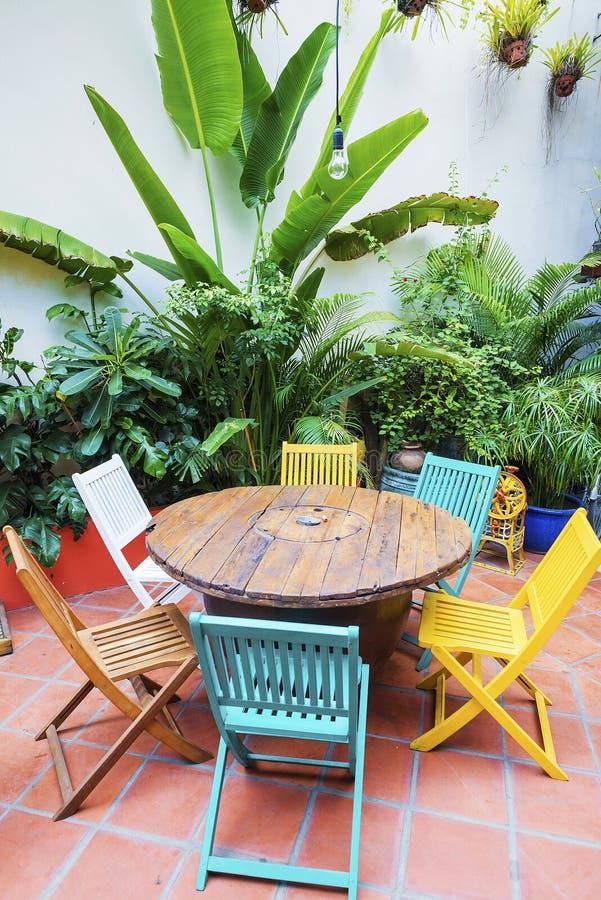 Sillas y tabla de madera brillantemente coloreadas en jardín foto de archivo