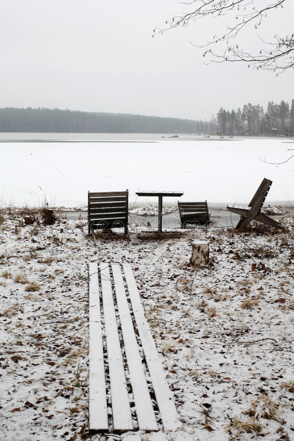 Sillas y tabla de madera en el lago congelado fotos de archivo