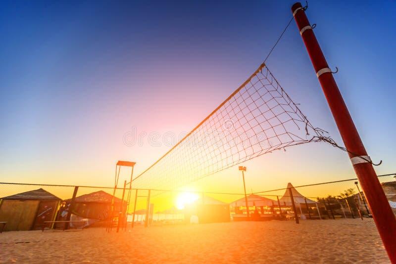 Sillhouette av en netto volleyboll och soluppgång på stranden fotografering för bildbyråer
