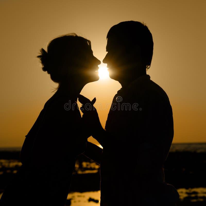 Sillhouette de pares de beijo no por do sol fotos de stock royalty free