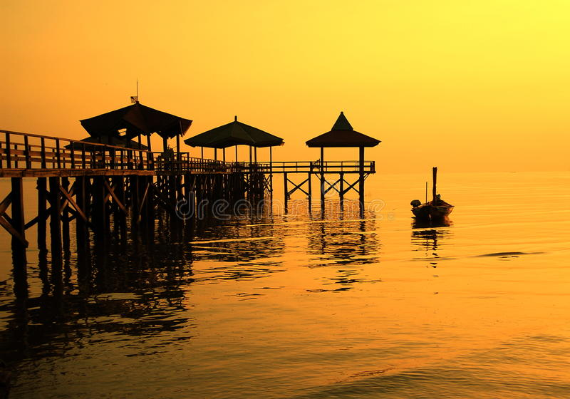 Sillhouette pier beside boat on the shore. Taken at Kenjeran beach, Surabaya, east Java, Indonesia royalty free stock photos