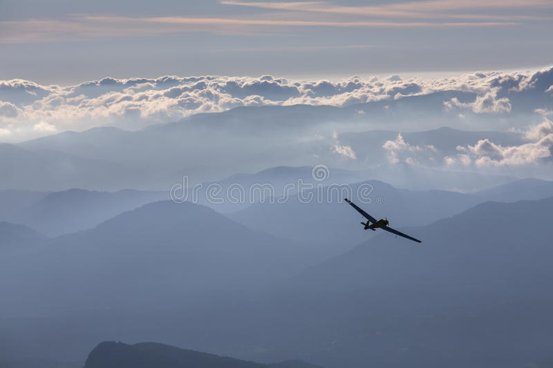 Sillhouette of small plane over clouds and mountains royalty free stock photography