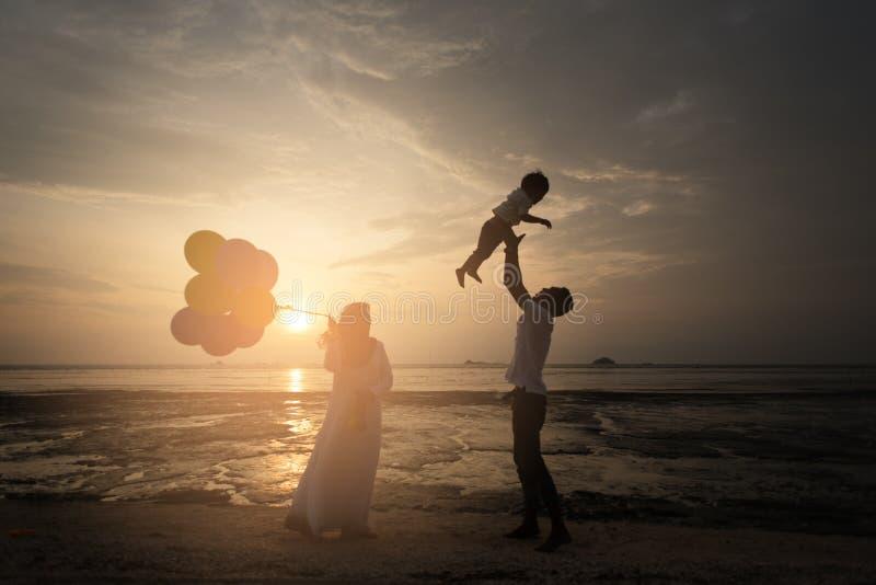 Sillhouette van gelukkige Aziatische familie die prettijd hebben bij het strand met zonsondergangmening als achtergrond royalty-vrije stock afbeeldingen