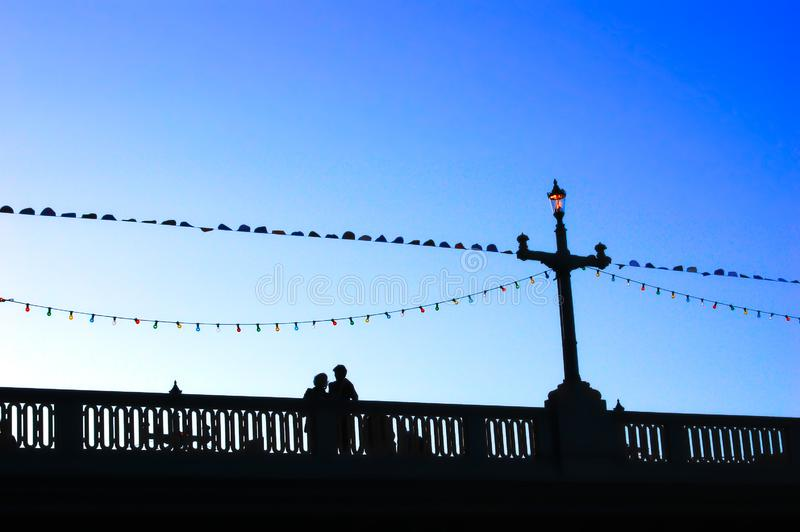 Sillhouetted couple and bridge iron works at sunset royalty free stock image