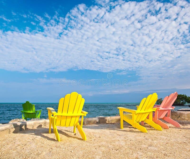 Sillones coloridos del amarillo y del rosa en una playa en la Florida