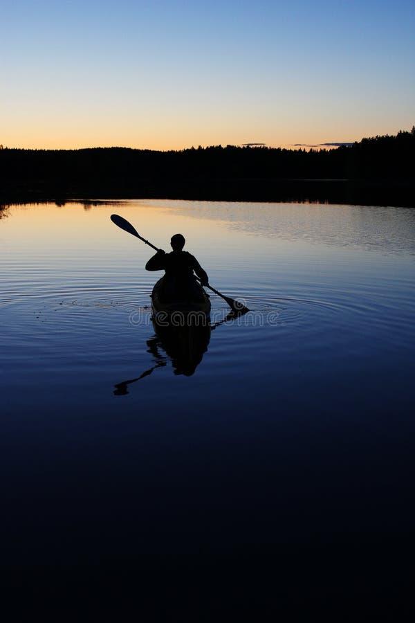 Sillouette del hombre kayaking en el lago fotos de archivo