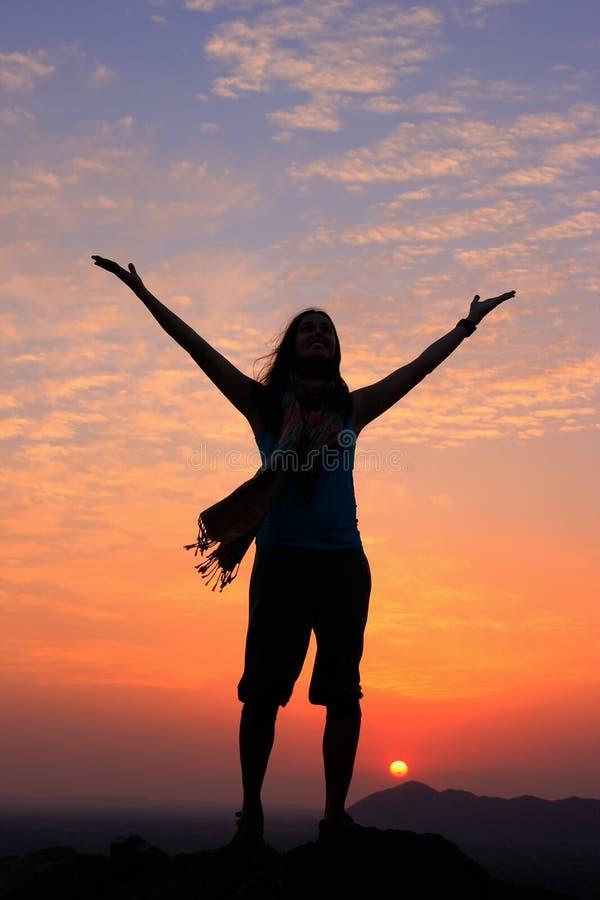 Sillouetted kobieta z ona ręki up przy zmierzchem na górze wzgórza, fotografia stock