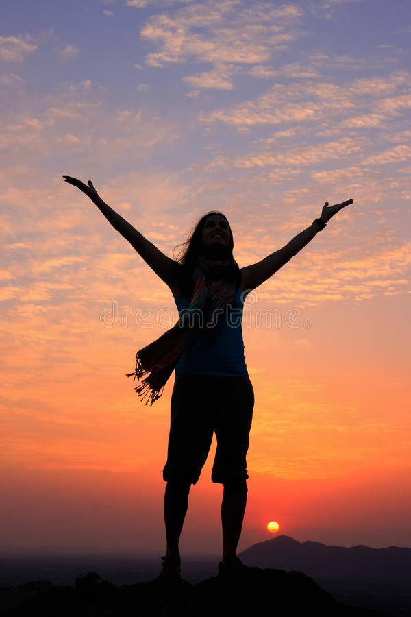 Sillouetted woman with her arms up at sunset on top of the hill, Pushkar, India stock photography