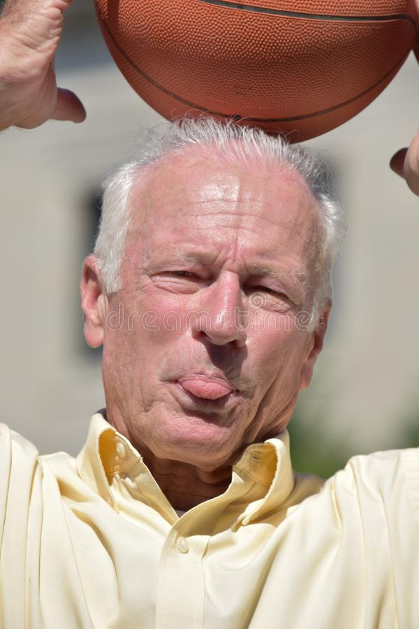 Silly Athlete Senior Male Basketball Coach With Basketball. A retired senior adult male royalty free stock image