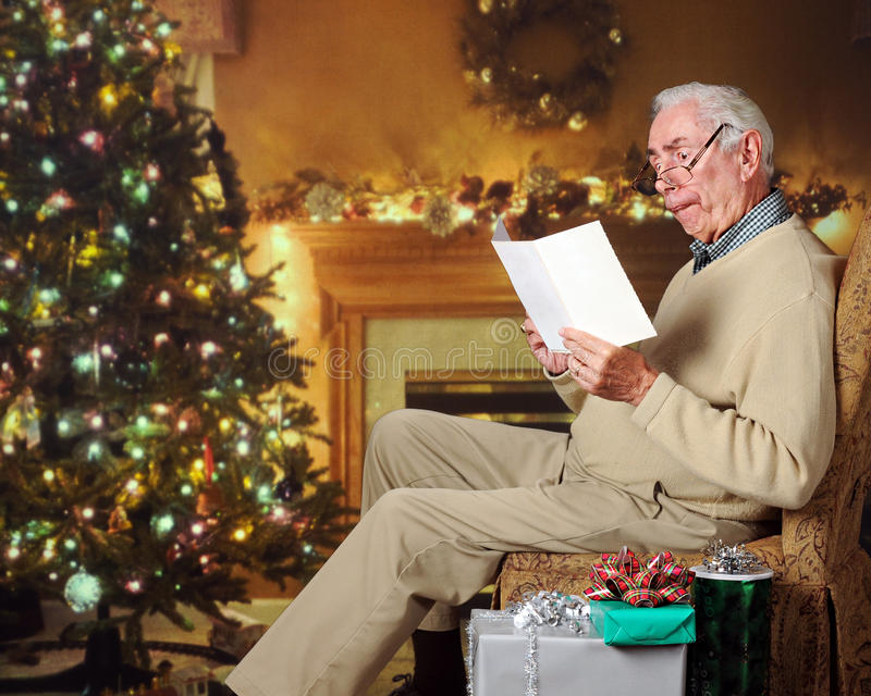 Silly Card Reader. A senior man acting silly, reading a card in a living room decorated for Christmas royalty free stock images