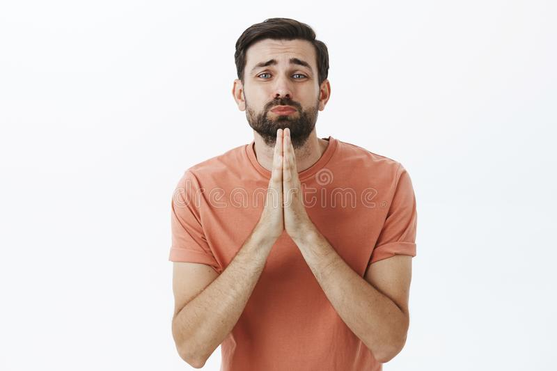 Silly and cute charming male asking for favor or help holding hands in pray folding lips and frowning begging apology. Standing in pink t-shirt over gray royalty free stock images