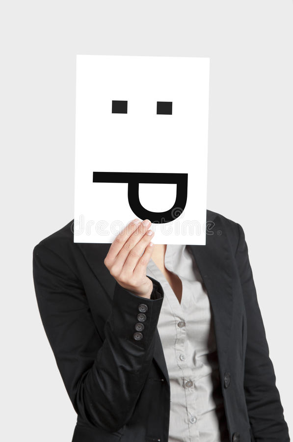 Silly emoticon. Woman showing a blank paper with a astonish emoticon in front of her face stock images