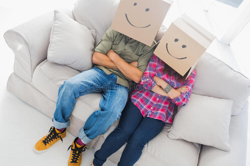 Silly employees with arms crossed wearing boxes on their heads stock photo