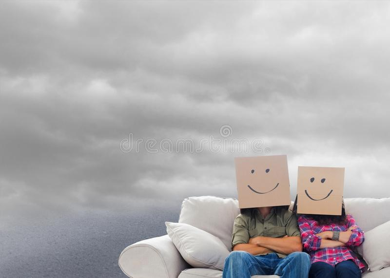 Silly employees with arms folded wearing boxes on their heads royalty free stock images