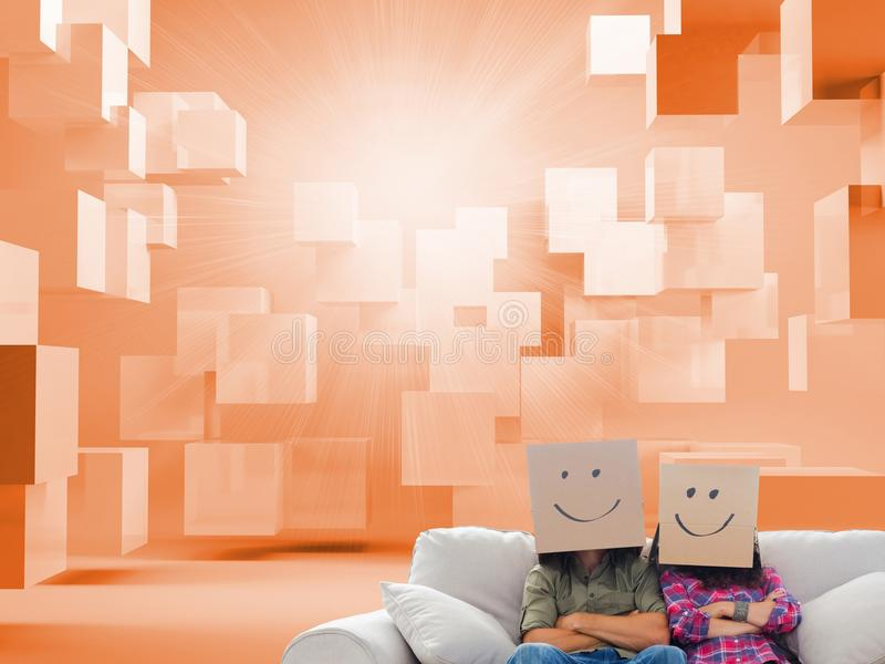 Silly employees with arms folded wearing boxes on their heads stock image
