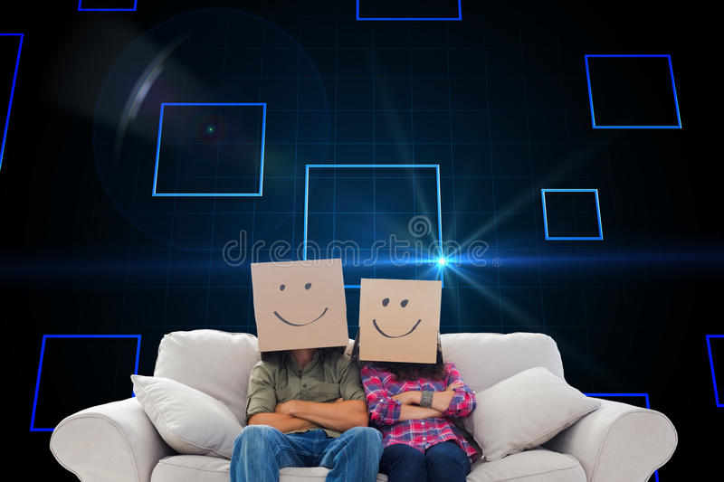Silly employees with arms folded wearing boxes on their heads stock images