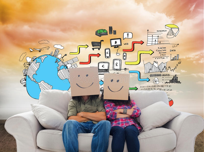 Silly employees with arms folded wearing boxes on their heads. Composite image of silly employees with arms folded wearing boxes on their heads with smiley faces royalty free stock photo