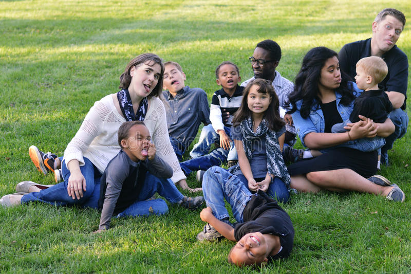 Silly Faces. A large, multi-racial, family with lots of adopted children playing in the grass and making funny faces royalty free stock photography
