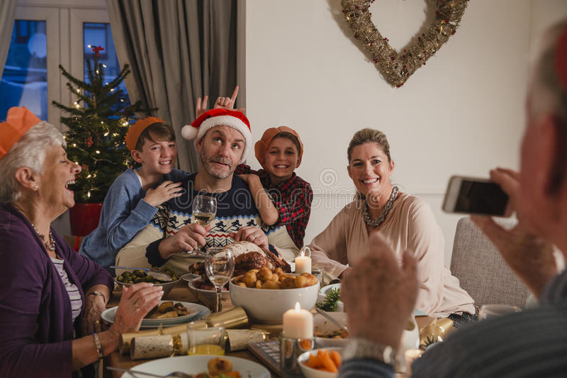 Silly Family Christmas Dinner Photo. Family are having Christmas dinner together. The grandfather is using a smartphone to take a silly photo of his family stock photo