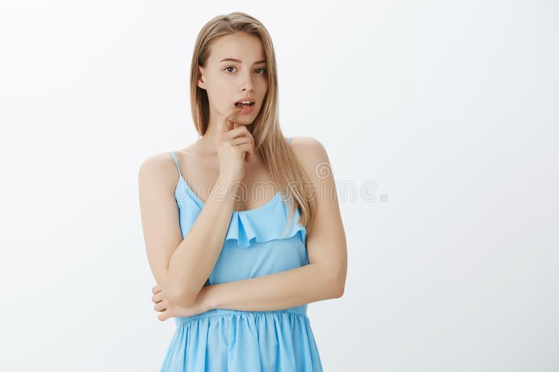 Silly good-looking european girl with fair hair and moles in blue dress open mouth and touching lip as spacing out. Thinking, making up plan posing gentle stock photography