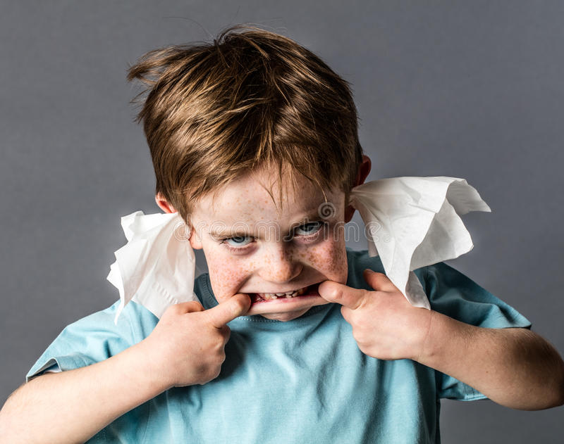 Silly kid with tissue in ears making grimace, not listening. Silly 5-year old red hair kid making a grimace with his big mouth, not listening with tissue in both stock images