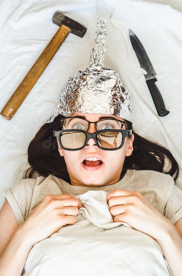 Silly paranoid woman wears tinfoil hat and sleeps with weapon and different glasses because of paranoia stock photography