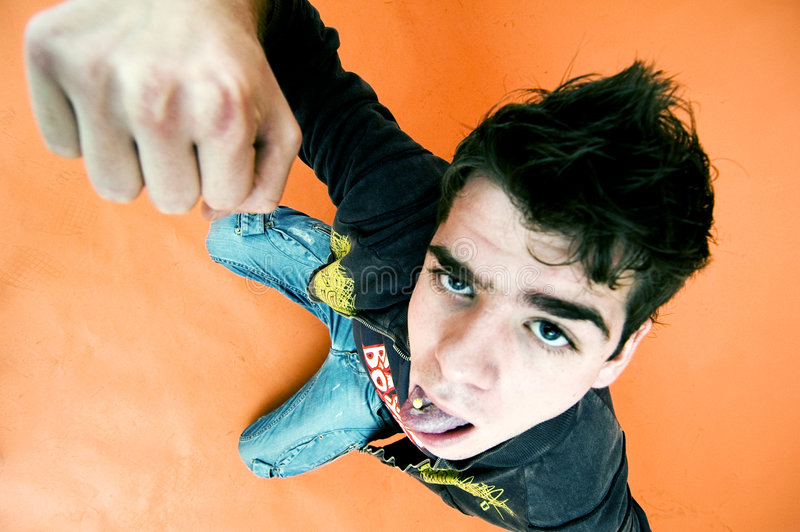 Silly Punching Man. Man with a silly expression holding his arm up in a punching position. Taken from high viewpoint looking down. Isolated on orange background stock photo