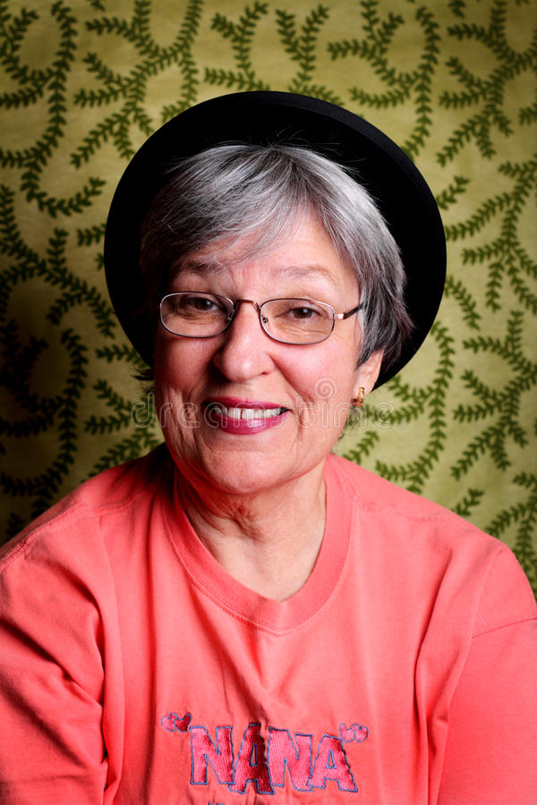 Silly Senior Lady. A silly pretty older lady with short grey hair, wearing glasses and a hat. Shallow depth of field stock images