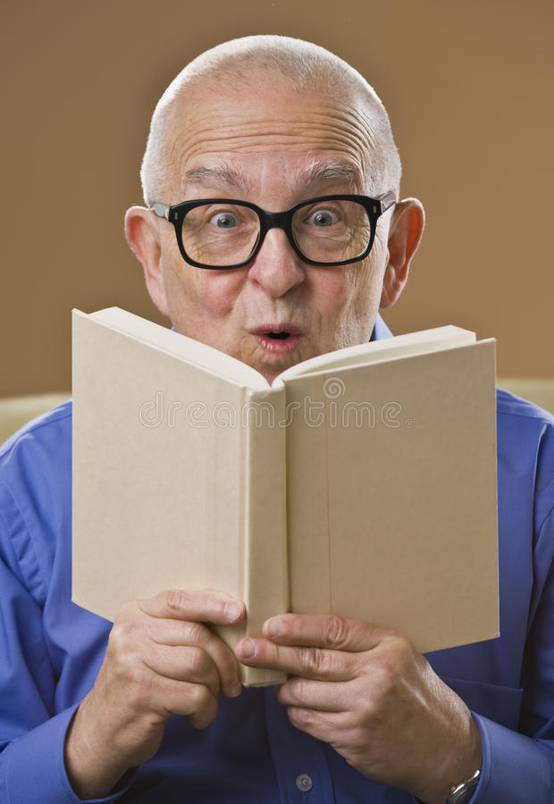 Silly senior man reading book. royalty free stock images
