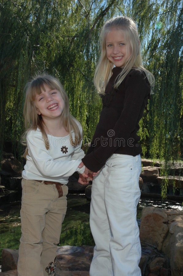 Silly Sisters. Two beautiful little blond sisters play and explore a nature area in a park. Spending time with family and being together. Two little girls stock images