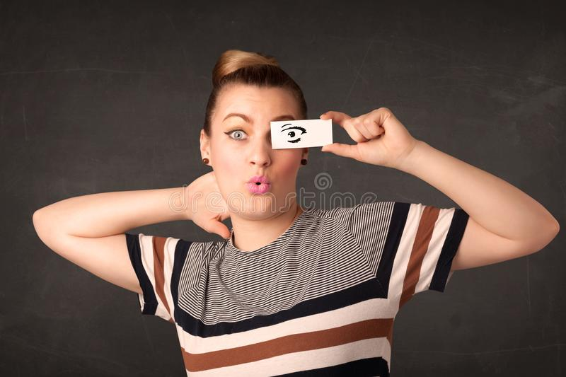 Silly youngster looking with hand drawn eye paper. Concept stock photos