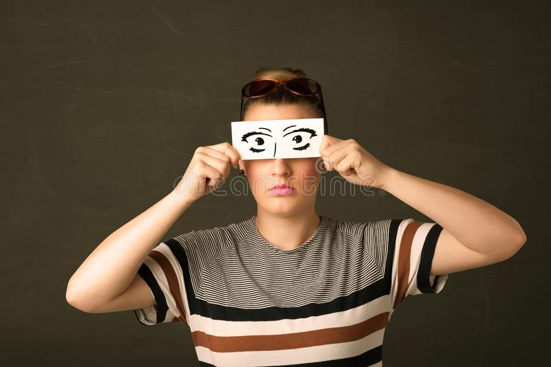 Silly youngster looking with hand drawn eye paper. Concept royalty free stock photo
