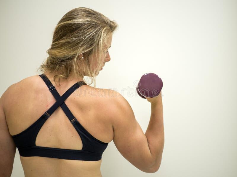 Silna żeńska kobieta robi bicep fryzuje dla ćwiczenia przy gym obraz stock