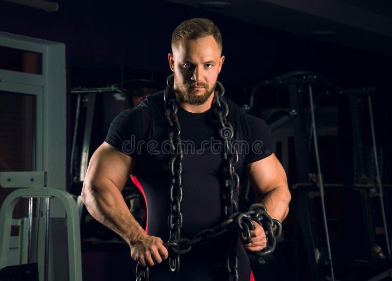 Silna atleta jest ubranym ławki wyposażenie z łańcuchem wokoło cześć zdjęcia stock