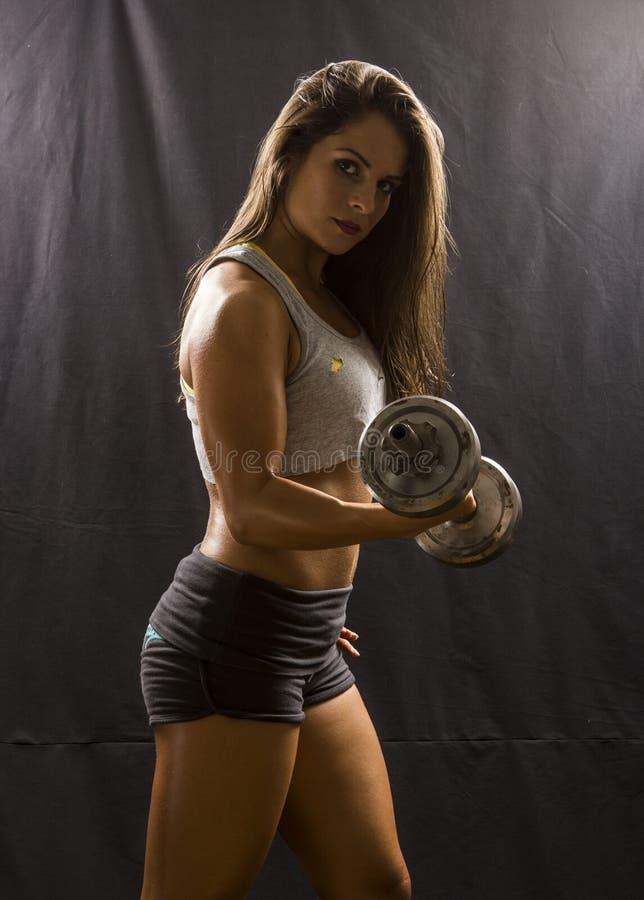 Silna kobieta robi bicepsa kędziorowi z dumbbell obrazy royalty free