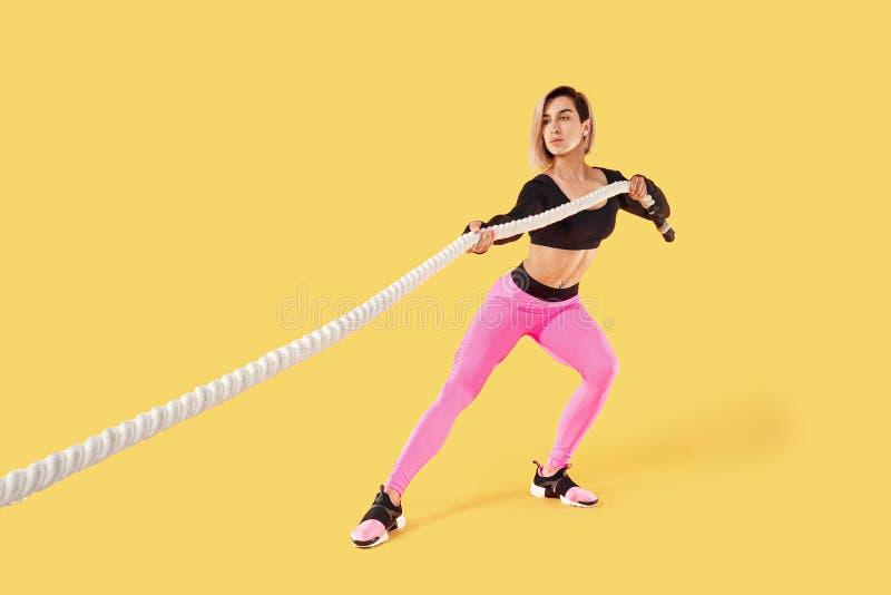 Silna kobiety ci?gni?cia arkana Fotografia sporty atrakcyjna kobieta w różowym i czarnym sportswear odizolowywającym na żółtym tl fotografia stock