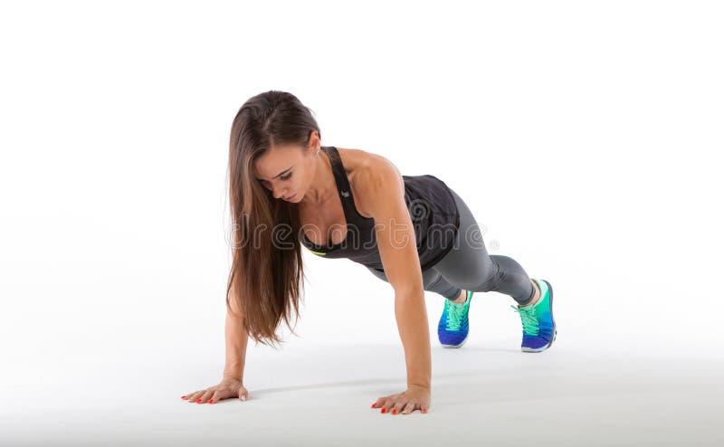 Silna młoda kobieta robi Ups Dysponowany żeński ćwiczyć w zdrowie klubie zdjęcie stock