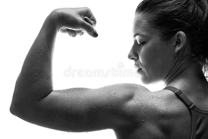 Silna mięśniowa sprawności fizycznej kobieta pokazuje bicepsy zdjęcia stock