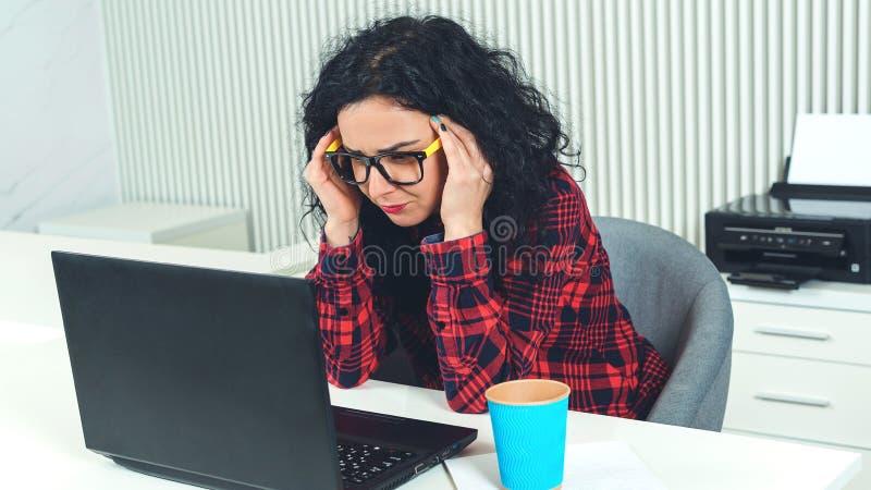 Silna migrena podczas pracy przy biurem Zm?czona biznesowa kobieta przy miejsce pracy biuro pracuje ci??ko dzie? mam b?le g?owy k zdjęcia stock