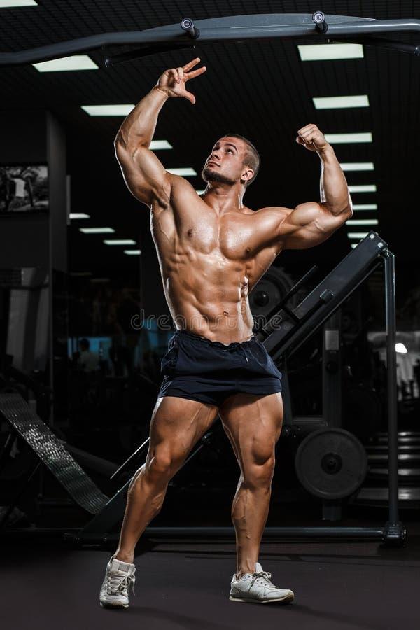 Silna Sportowa mężczyzna sprawności fizycznej modela półpostać pokazuje mięśnie w gym zdjęcia stock
